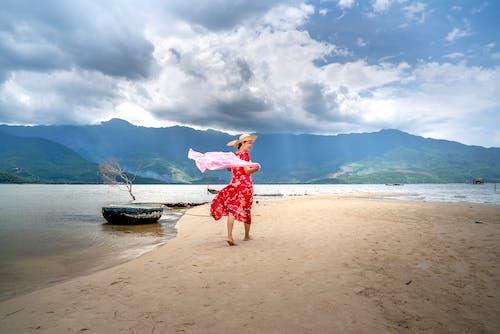 Traveler with flying fabric walking on sea shore against ridge