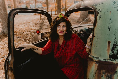 Woman in Red and Black Checkered Dress Shirt Sitting on Black Car