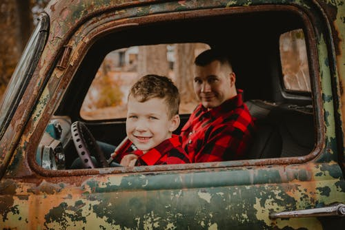 Boy in Red and Black Plaid Shirt Sitting on Car Seat