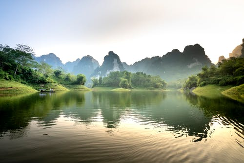 Picturesque landscape of traditional boat floating on rippling lake amidst rocky mountains covered with lush green trees against cloudless sunset sky