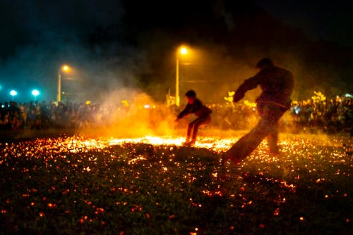 People running on ground with burning coals in night time