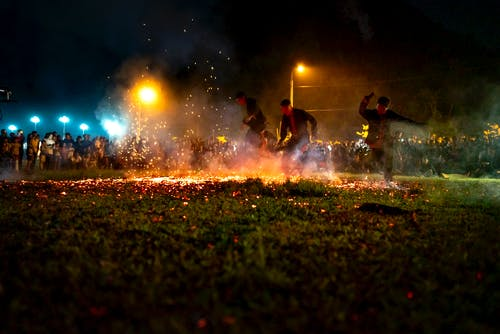 Men in casual clothes running on hot burning coals placed on grass during night show