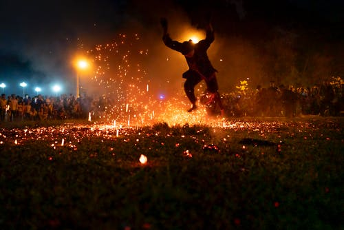 Man with raised hands jumping on smoldering coals