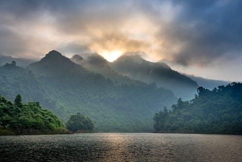 Green hills surrounding rippling lake under clouds