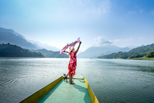 Woman with pet enjoying vacation in lake in hilly terrain