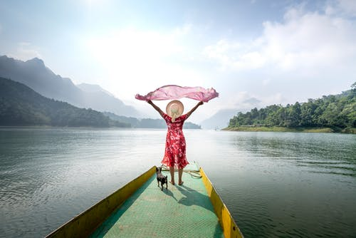 Full body back view of unrecognizable female traveler standing on pier with waving pareo near dog and enjoying view of lake and hills