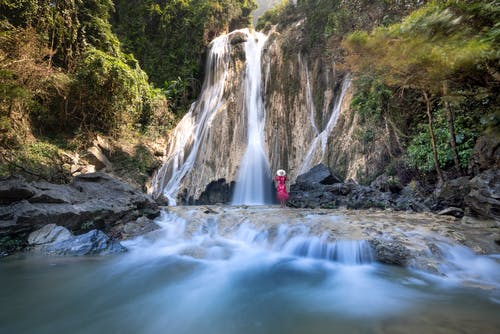 Unrecognizable traveler admiring foamy waterfall in mountains