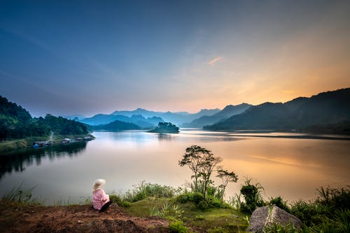 Back view of anonymous female tourist contemplating river and mount silhouettes in fog under cloudy sky at sundown