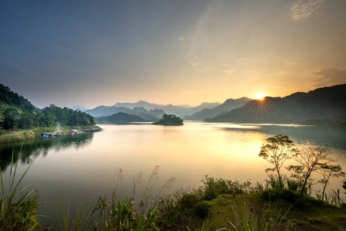 Scenery view of lake against high mount silhouettes in fog under cloudy sky with shiny sun in evening