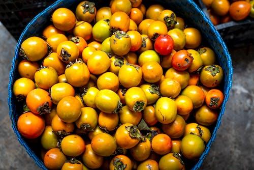 Pile of fresh sweet persimmons in basket
