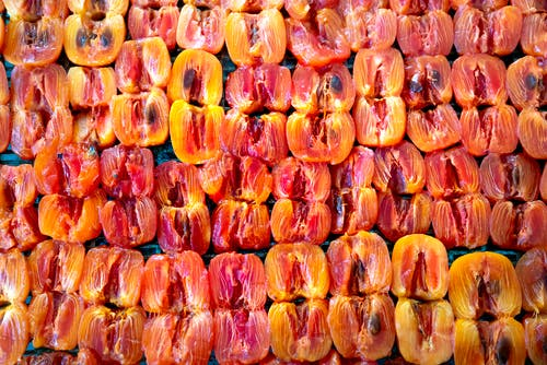 From above of pile of fresh ripe juicy halved persimmons placed on stall and sun drying