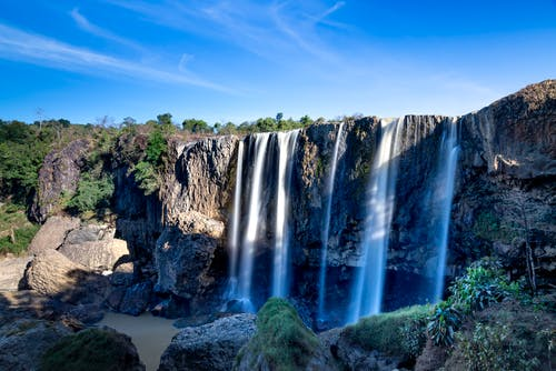 Scenic view of waterfalls with fast aqua fluids on rugged mount under blue sky in sunshine
