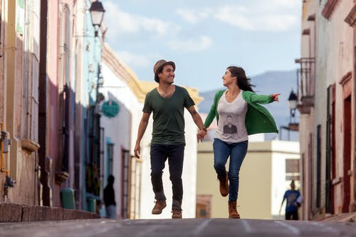 Man in Green Crew Neck T-shirt and Blue Denim Jeans Holding Woman in Green Tank