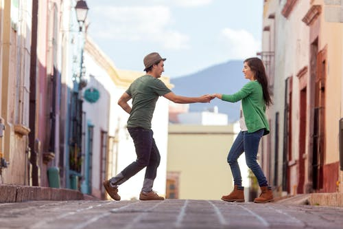 Man in Green T-shirt and Woman in Green T-shirt Walking on Gray Concrete Pavement