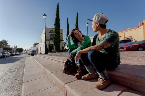 Man in Green T-shirt and Black Pants Sitting on Concrete Bench
