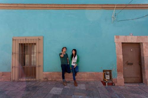 Woman in Black Jacket Standing Beside Blue Painted Wall