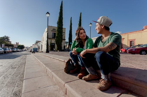 Man in Green Crew Neck T-shirt Sitting on Concrete Bench