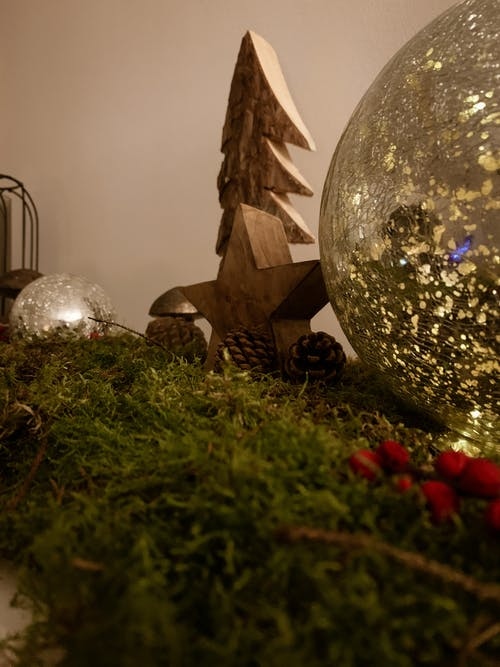 Christmas decoration with wooden toys and baubles arranged with coniferous branches