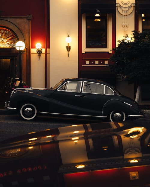 Luxury retro cars parked outside classy building in evening