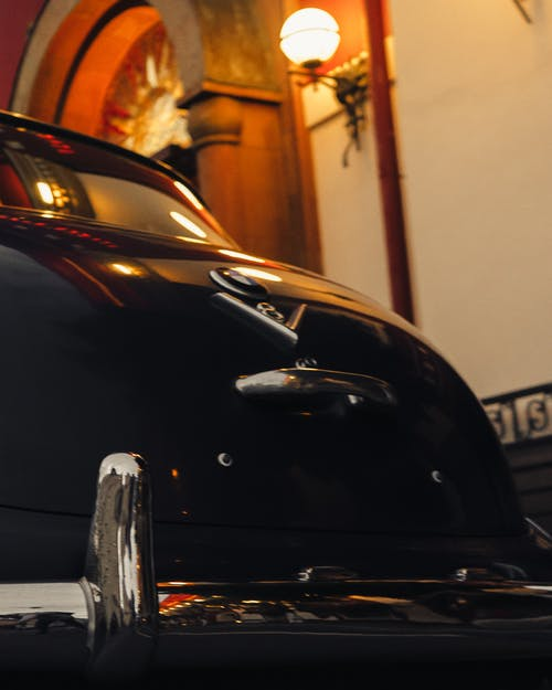 From below of old fashioned clean black car with metallic bumper parked parked near expensive mansion with lamps on facade at night