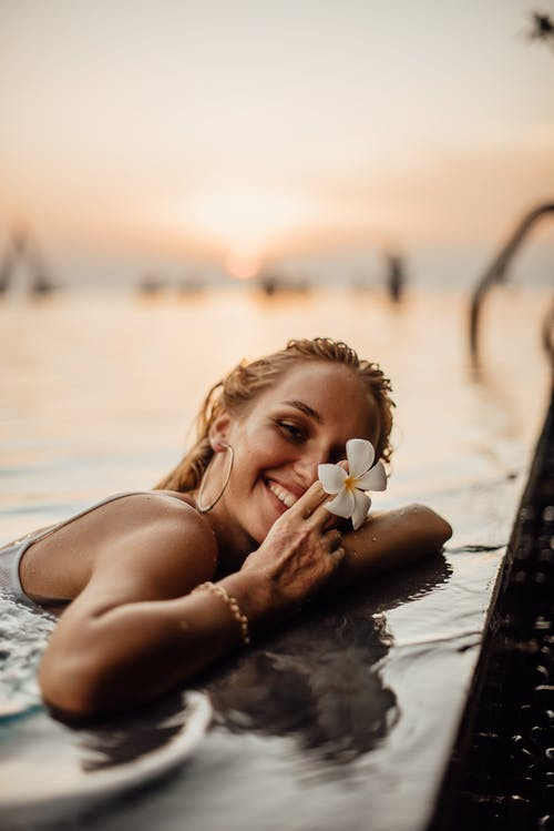 A Woman by the Poolside Holding a Flower