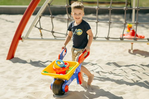 A Boy Playing in the Sand withy Toys