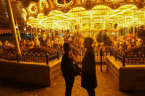 A Couple Standing in Front of a Carousel