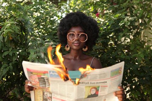 Trendy black woman reading burning newspaper in garden