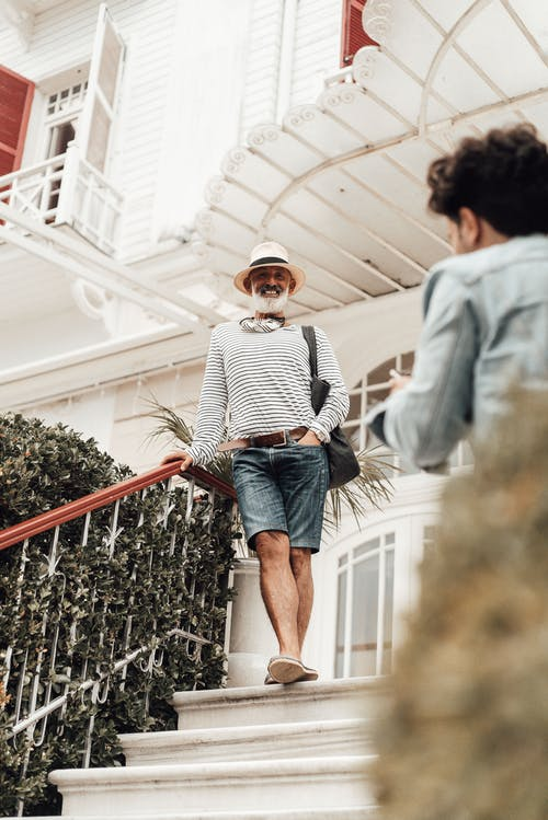 Full body smiling senior ethnic male in stylish summer clothes and hat leaning on stairway railing outside modern hotel building and looking at camera happily