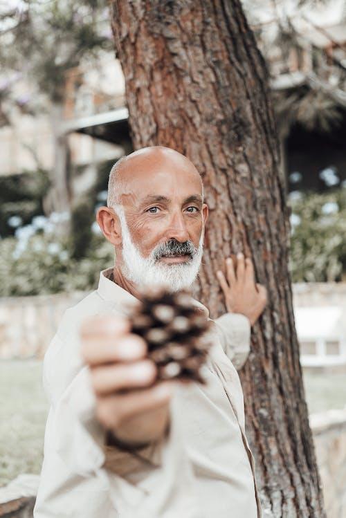 Positive senior man demonstrating cone in garden