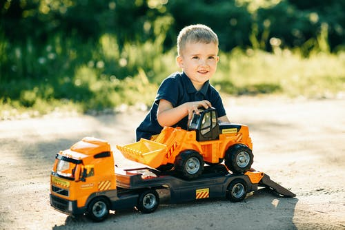 A Boy Playing with Toy Trucks
