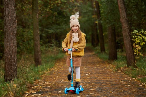 Girl in Brown Coat and Blue Denim Jeans Riding Bicycle on Dirt Road
