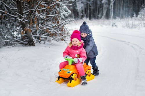 Child in Black Jacket Riding Red and Yellow Ride on Toy on Snow Covered Ground during