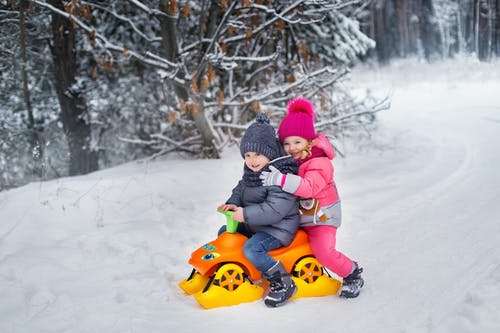 Child in Red Jacket Riding Yellow and Red Ride on Toy on Snow Covered Ground during