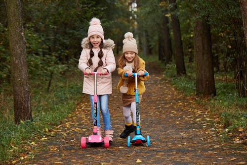 Girl in Pink Jacket Riding Red and Blue Kick Scooter