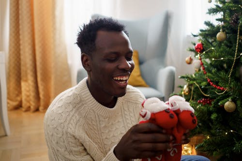 A Man in White Sweater Smiling While Holding a Red Christmas Socks