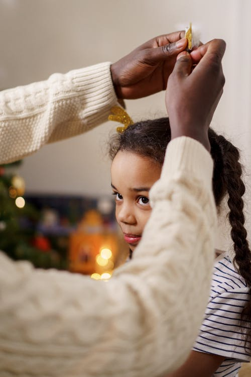 A Person Putting on Antlers Hair Pin on Her Daughter's Head