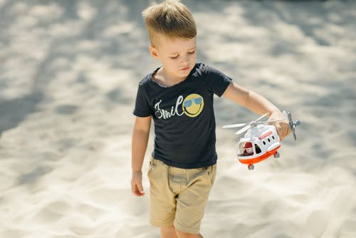 Boy in Blue Crew Neck T-shirt and Brown Cargo Shorts Holding White and Red Toy