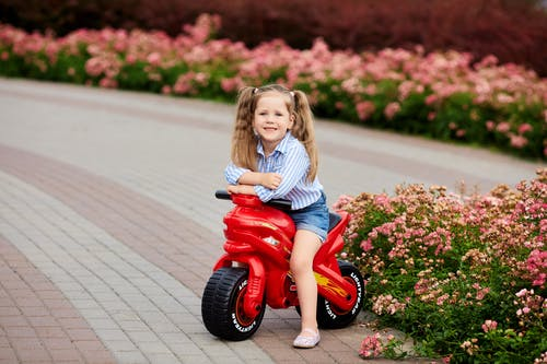 Girl in Blue Denim Jacket and Blue Denim Jeans Riding Red Ride on Toy Car