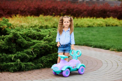 Girl in Blue Denim Shorts Riding Pink and Purple Ride on Toy