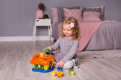 Girl in Gray Sweater Playing With Orange and Blue Plastic Toy