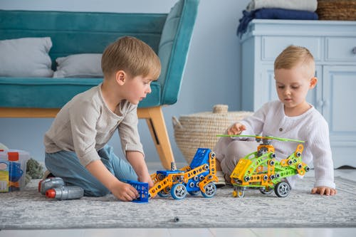 Boy in Gray Crew Neck T-shirt Playing With Blue and Yellow Toy Car