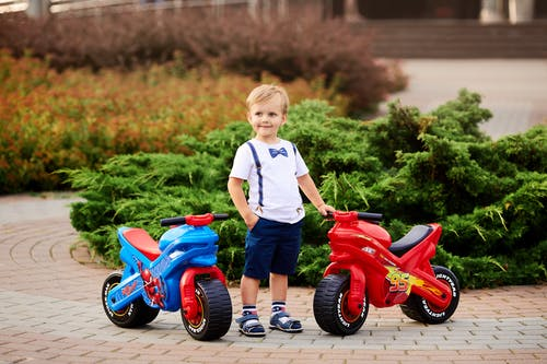 Boy in White Crew Neck T-shirt and Blue Shorts Standing Beside Red and Black Ride