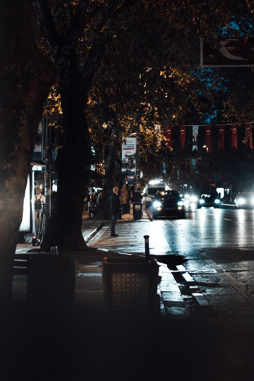 Side view of unrecognizable male standing in street near cars riding on wet asphalt road in modern city at night