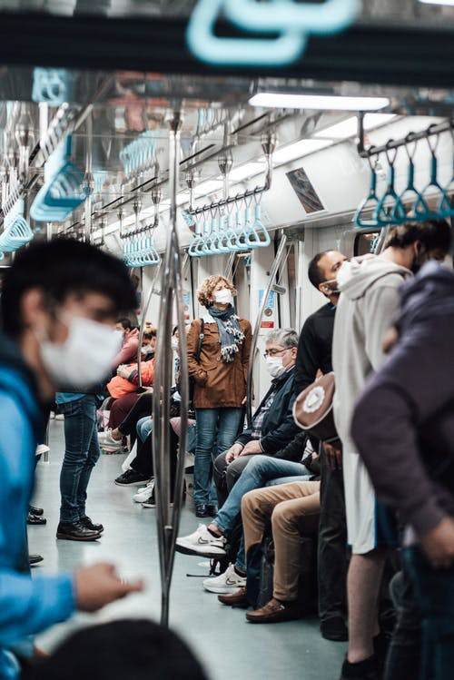 Anonymous people in masks riding train during COVID 19