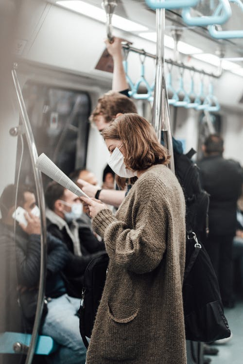 Side view of unrecognizable concentrated lady in casual clothes and medical mask reading newspaper while commuting y subway train with male passengers