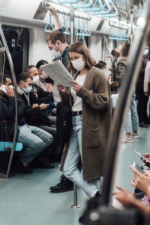Anonymous woman in sterile mask reading newspaper near crop passengers on subway during COVID 19 pandemic