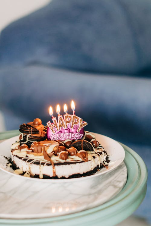 White and Brown Cake With Candles on White Ceramic Round Plate