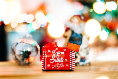 Red and White Gift Box on Brown Wooden Table