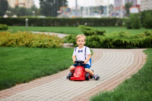 Boy in White T-shirt Riding Red Ride on Toy Car on Brown Brick Pathway during